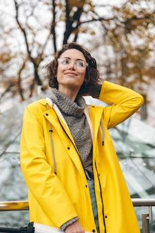 Mulher linda com um lindo cabelo encaracolado, andando pelo centro da cidade no fim de semana, tendo prazer enquanto passa um tempo sozinha