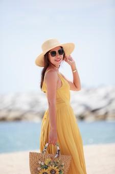 Mulher linda com um vestido amarelo em pé e feliz sorrindo para o mar