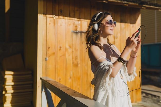 Mulher linda com vestido branco de verão ouvindo música em fones de ouvido, dançando e se divertindo, segurando o smartphone, estilo férias de verão