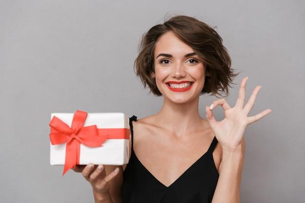 Mulher linda com vestido preto segurando uma caixa de presente, isolada sobre uma parede cinza