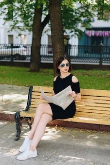 Mulher linda de vestido preto no parque com jornal