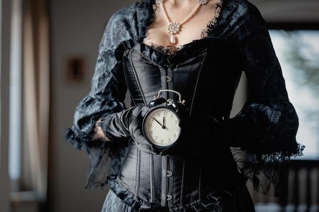 Mulher linda de vestido preto segurando um despertador vintage no interior