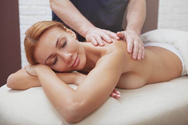 Mulher linda, desfrutando de massagem de corpo inteiro no centro de spa