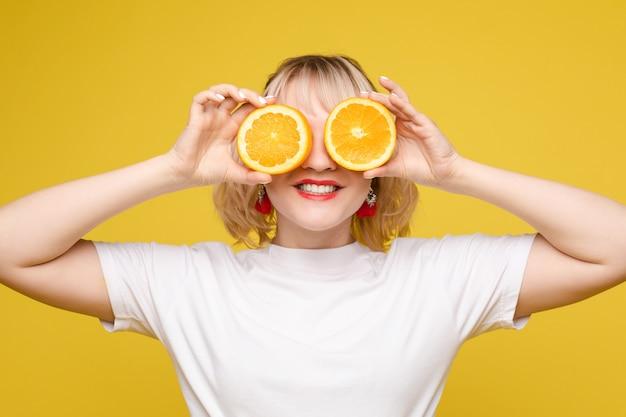 Mulher linda e alegre brincando com fatias de laranja. círculos laranja. anúncios de suco. moldura alegre. fundo amarelo