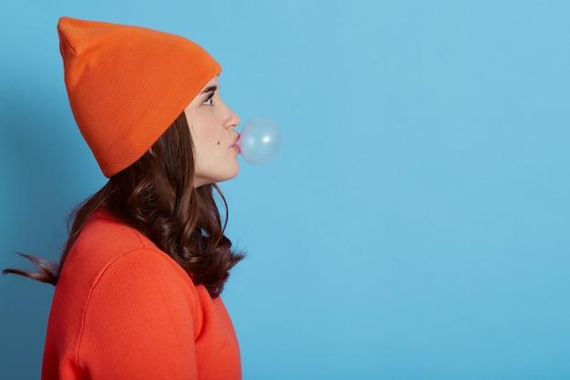 Mulher linda e atraente soprando chiclete, posando em azul, vista lateral de uma senhora com chiclete