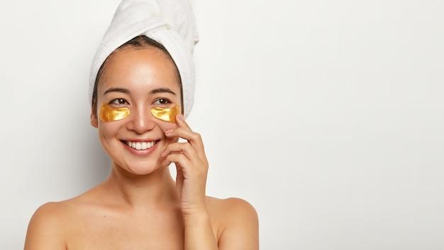 Mulher linda e charmosa com pele sã, aplica adesivos cosméticos embaixo dos olhos, olha alegremente para o lado, pensa em algo agradável, usa toalha enrolada na cabeça, tem procedimentos de spa em casa