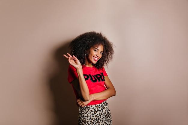 Mulher linda e elegante em uma camiseta em pé no estúdio e rindo