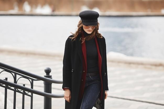 Mulher linda e elegante modelo, de boné, casaco e óculos escuros, posando para a paisagem urbana.