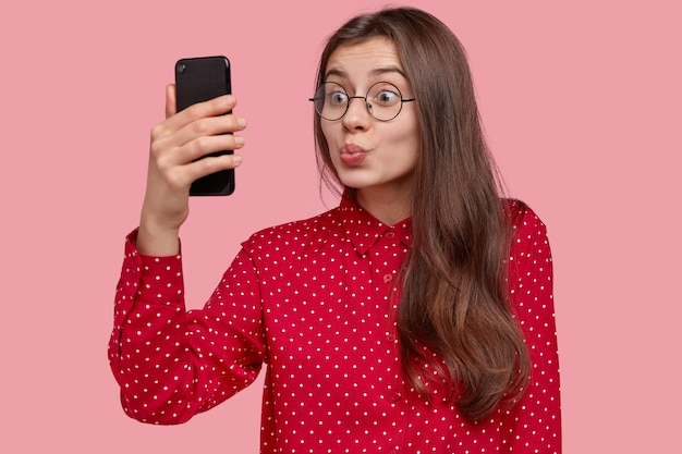 Mulher linda e encantadora tira selfie no celular, faz beicinho na câmera, usa óculos ópticos redondos, aproveita o tempo livre