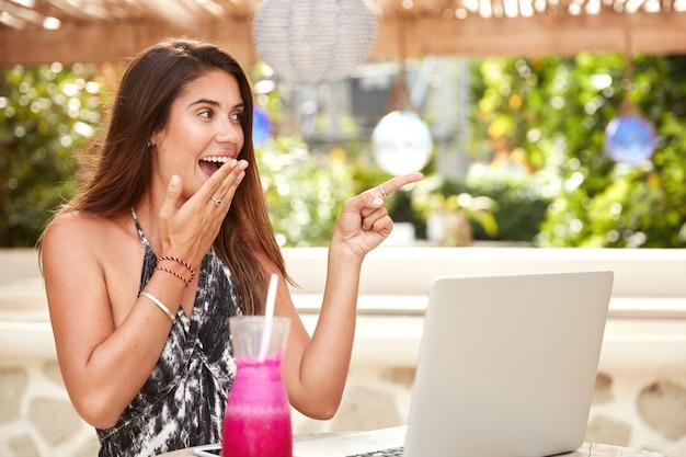 Mulher linda e espantada olhando com entusiasmo para longe, trabalhando em um laptop