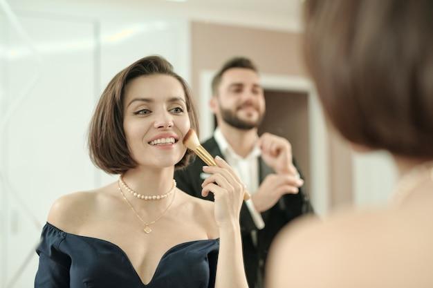 Mulher linda e feliz aplicando maquiagem com pincel em frente ao espelho enquanto o namorado ajeita a manga da camisa