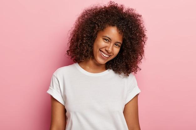 Mulher linda e linda com pele saudável, cabelo crespo e encaracolado, inclina a cabeça, sorri feliz, tem pouco espaço entre os dentes, expressa boas emoções, gosta de posar, usa camiseta branca casual
