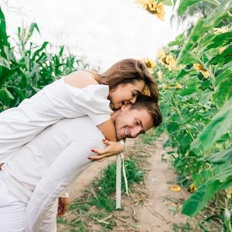 Mulher linda e linda e elegante casal rústico em um campo de girassóis se beijando, terno