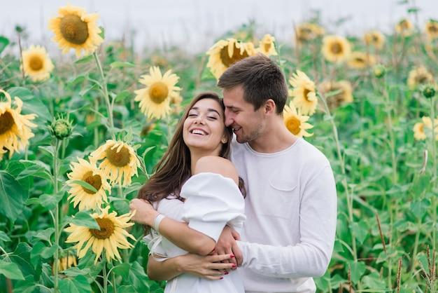 Mulher linda e linda e elegante casal rústico em um campo de girassóis se beijando, terno Foto Premium