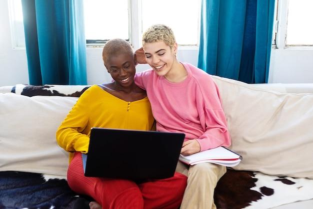 Mulher linda e melhor amiga com um laptop descansando no sofá enquanto usa um laptop em casa