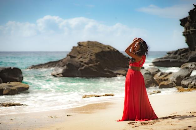 Mulher linda e sensual usando um vestido vermelho luxuoso e posando ao lado de um penhasco de areia