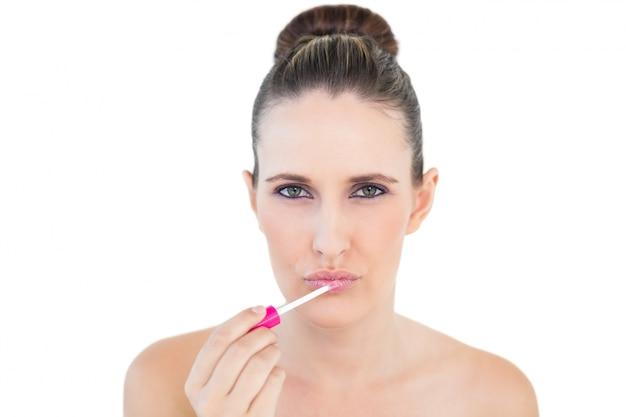 Mulher linda e séria aplicando brilho labial