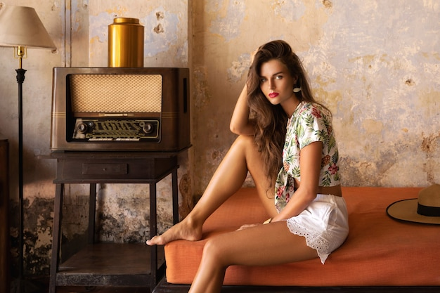 Mulher linda e sexy sentada no sofá na sala vintage