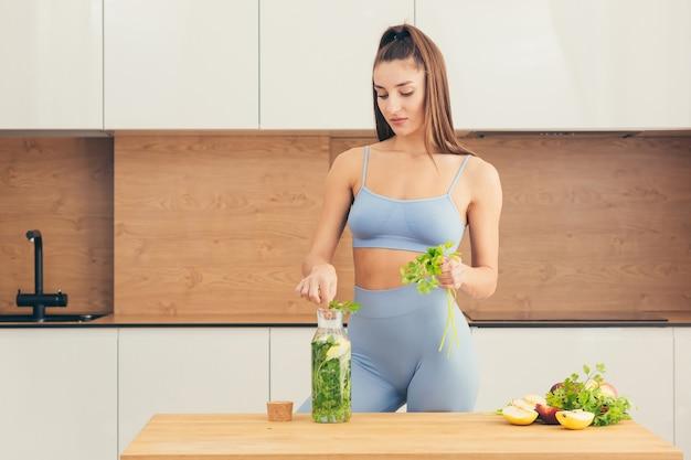 Mulher linda em fitness preparando comida saudável em casa