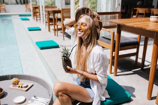 Mulher linda em óculos de sol se passando perto da piscina com abacaxi. incrível turista feminina de cabelos compridos relaxando no resort com coquetel de frutas.