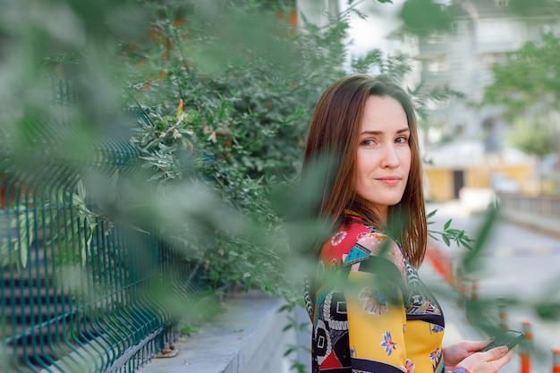 Mulher linda em pé e olhando na rua em vestido colorido