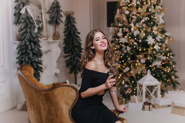 Mulher linda em roupa preta, sentada no sofá marrom com um copo de vinho. retrato de menina de cabelos compridos confiante, comemorando as férias de inverno com árvore de natal na parede.