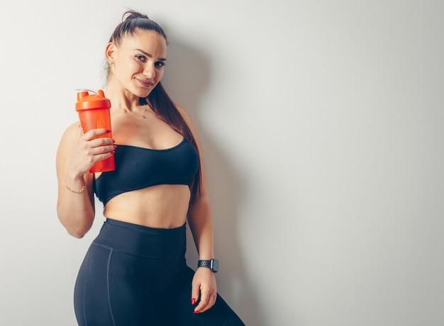 Mulher linda em terno preto esportes em pé e segurando a caneca laranja