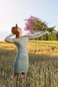 Mulher linda em um lindo vestido azul, chapéu preto e um enorme buquê de flores silvestres roxas ri ao ar livre em um prado