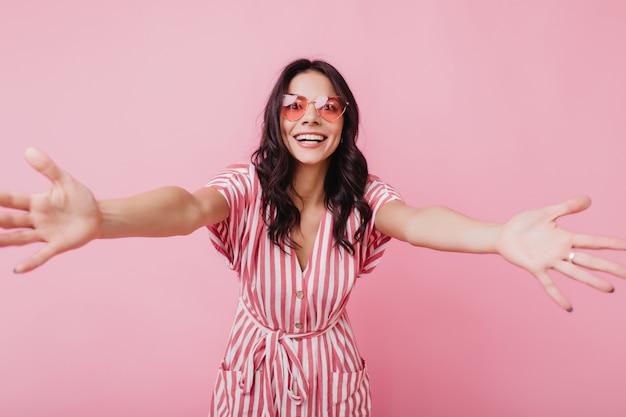 Mulher linda em um traje de verão rosa expressando boas emoções. foto de senhora morena relaxada isolada.