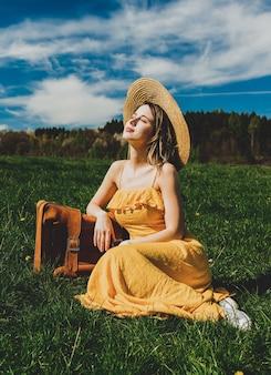 Mulher linda em um vestido amarelo e uma mala sentada num prado de montanha com flores