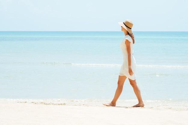 Mulher linda em um vestido branco caminhando na praia