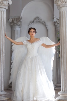 Mulher linda em um vestido branco com asas de anjo nas costas dela. ele fica em uma bela decoração contra a parede.