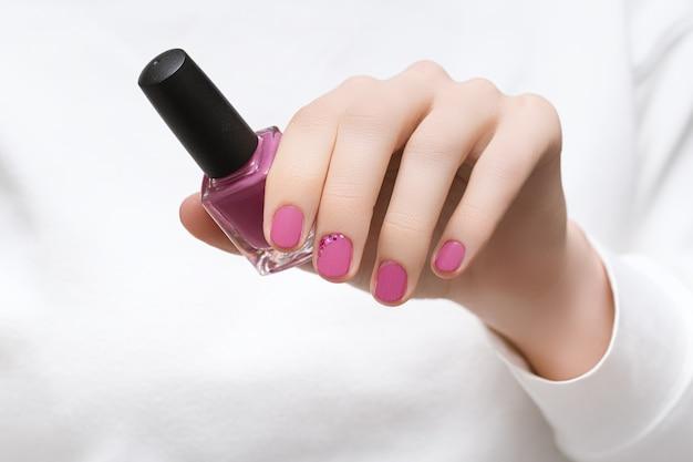 Mulher linda em um vestido branco com design de unhas rosa perfeito segurando o frasco de esmalte rosa.