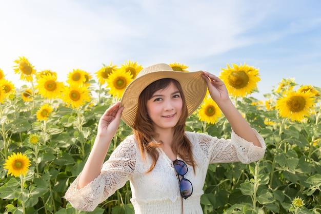 Mulher linda em um vestido branco em um campo de girassóis de verão