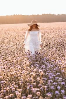 Mulher linda em um vestido branco em um campo de lavanda ao pôr do sol