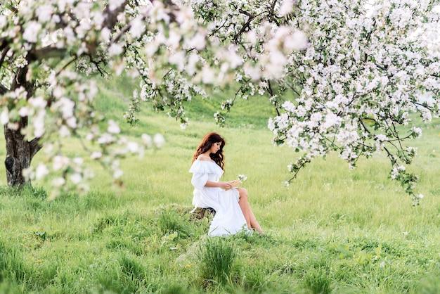 Mulher linda em um vestido branco lê um livro no jardim primavera. uma garota no fundo de árvores floridas.