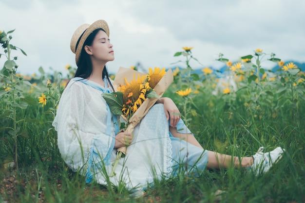 Mulher linda em um vestido branco no campo de girassol