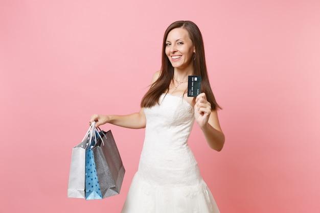 Mulher linda em um vestido branco segurando um cartão de crédito e sacolas de pacotes multicoloridos com compras após as compras