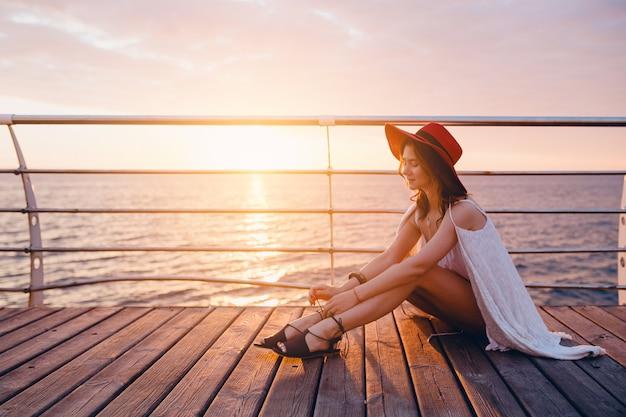 Mulher linda em um vestido branco sentada à beira-mar ao nascer do sol num clima romântico