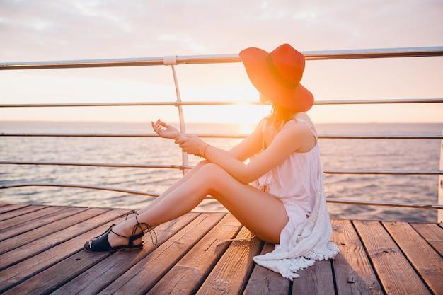 Mulher linda em um vestido branco sentada à beira-mar no nascer do sol em clima romântico usando chapéu vermelho