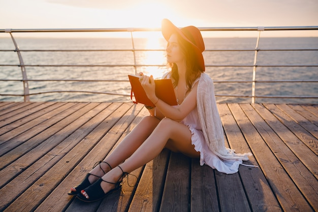 Mulher linda em um vestido branco sentada à beira-mar no nascer do sol pensando e fazendo anotações no livro diário