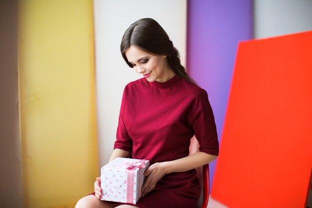 Mulher linda em um vestido cor de vinho, segurando uma caixa de presente. conceito de férias.
