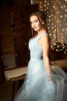 Mulher linda em um vestido de noite azul em um fundo de guirlandas conceito de ano novo e natal