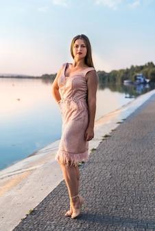 Mulher linda em um vestido elegante na praia ao pôr do sol