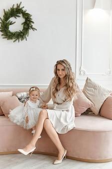 Mulher linda em um vestido elegante, posando com sua filha em um vestido fofo no interior decorado de natal.