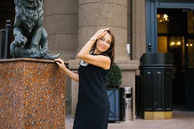 Mulher linda em um vestido escuro está sorrindo e feliz