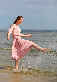 Mulher linda em um vestido longo na praia