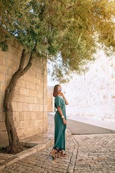 Mulher linda em um vestido longo verde em pé no parque perto da árvore e parede de pedra