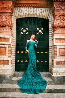 Mulher linda em um vestido longo verde na arquitetura antiga