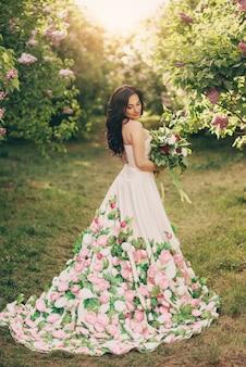 Mulher linda em um vestido luxuoso está em um jardim lilás florido